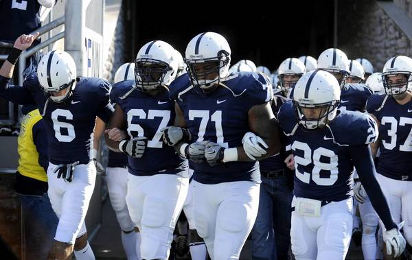 With heads held low, Penn State seniors Derek Moye, Quinn Barham, Devon Still, and Drew Astorino lead the team into the stadium. The Nebraska Cornhuskers defeated the Penn State Nittany Lions, 17-14, at Beaver Stadium in State College, Pennsylvania, Saturday, November 12, 2011.