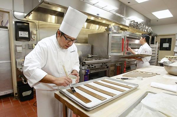 Pastry chef Andy de la Cruz applies molasses to strips of gingerbread made to look like pieces of wood in the Island Hotel pastry kitchen.