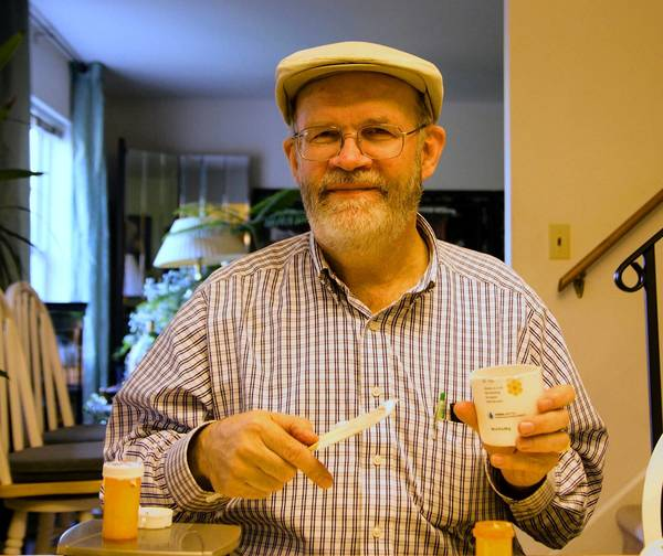 Karl Wacker, of Easton, cuts open empty lotion bottles and scrapes the remaining lotion into empty pill bottles.