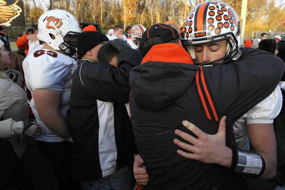 Washington quarterback Colton Marshall, right, gets a hug from his dad Curtis after he and his team lost a 5A football semifinal game between Washington Community High School and Sacred Heart-Griffin in Springfield. The Sacred Heart-Griffin Cyclones won 44-14.