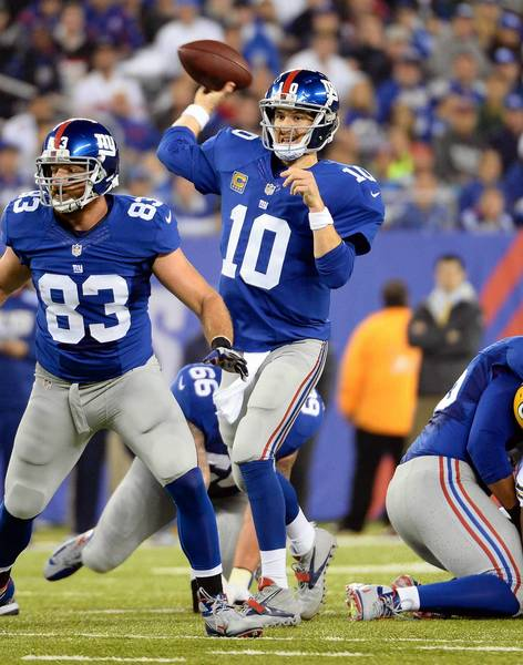 Nov 17, 2013; East Rutherford, NJ, USA; New York Giants quarterback Eli Manning (10) throws a touchdown pass during the first quarter agains the Green Bay Packers at MetLife Stadium.