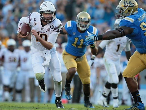 UCLA defensive tackle Ellis McCarthy can't get a hand on Arizona State quarterback Taylor Kelly as he runs for a touchdown in the first quarter.