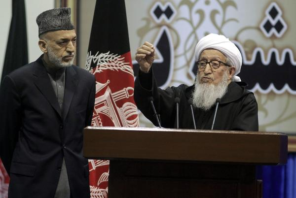 Afghan President Hamid Karzai, left, and Chairman Sibghatullah Mojaddedi, chairman of the loya jirga assembly, speak to the audience on the final day of the jirga in Kabul.