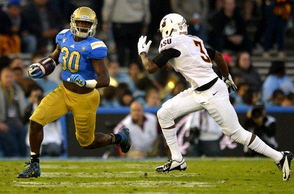UCLA's Myles Jack tries to turn the corner on Arizona State defensive back Damarious Randall in the first half Saturday at the Rose Bowl.