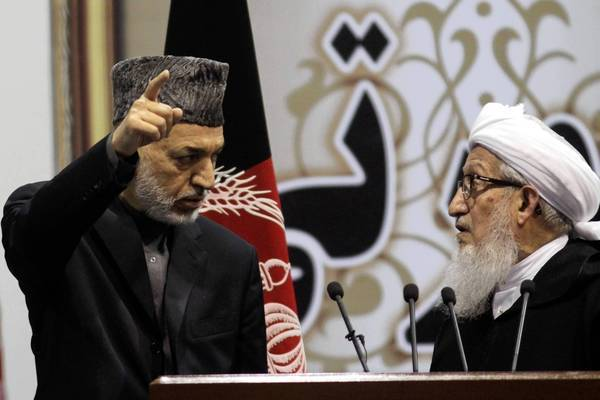 """Afghan President Hamid Karzai, left, talks with Sibghatullah Mojaddedi, the chairman of the loya jirga, in Kabul. At one point, Mojaddedi lectured Karzai, warning that if he delays signing the security deal with the U.S., """"I'll resign and leave the country."""""""