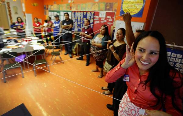 New Open World Academy first grade teacher Bianca Sanchez, right, listens for names during a icebreaker game using yarn with parents.