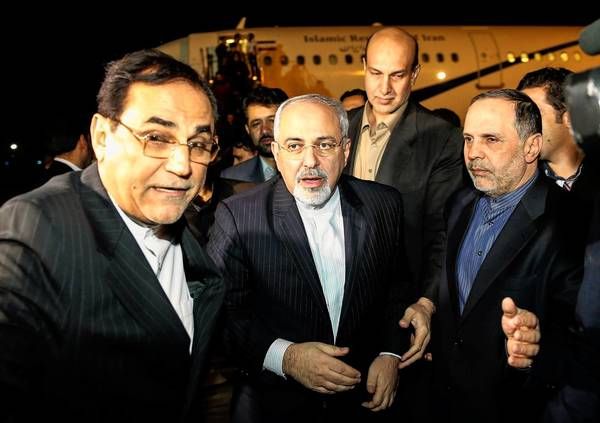 Iranian Foreign Minister Mohammad Javad Zarif, center, arrives at Tehran's Mehrabad airport after talks in Geneva in which world powers reached a preliminary agreement on Iran's nuclear program.