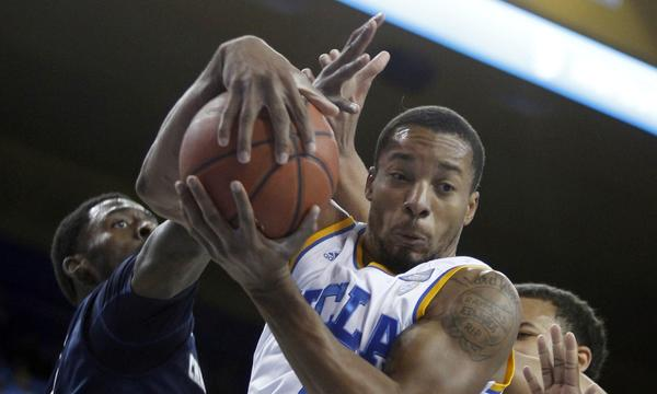 UCLA guard Norman Powell pulls down a rebound in front of Chattanooga guard Casey Jones, left, during the Bruins' blowout victory Sunday.