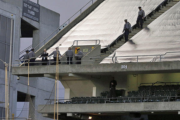 Law enforcement officials walk in the upper deck of Oakland's Coliseum on Sunday.