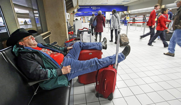 David McCain of Abilene, Texas, relaxes in the seats of the ticketing area for American Airlines in Terminal C at Dallas-Fort Worth Airport after his flight home was canceled. A cold front began to move into the North Texas area Sunday, which could affect Thanksgiving travel as it heads east.