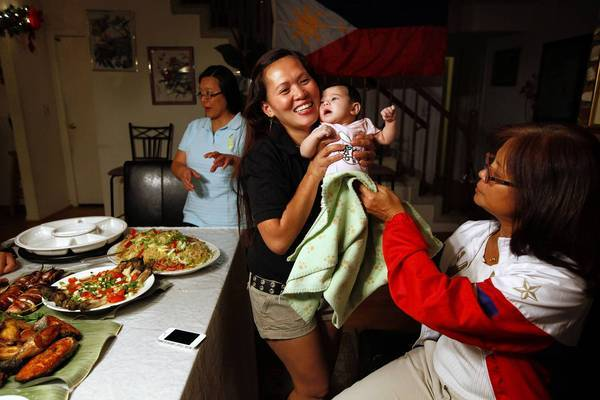 Host Flor Ross takes her baby Mary Catherine, 2 months, from Agnes Ma, right, at a Manny Pacquiao party at Ross' Arcadia home. Pacquiao is a national hero in the Philippines, and his victory over Mexican American boxer Brandon Rios was a morale-booster for a country devastated by Typhoon Haiyan.