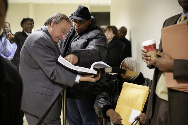 Lawyer Tom Jaconetty, left, reviews nomination paperwork and petitions as candidates and volunteers wait in line at the Cook County Administration Building in Chicago.