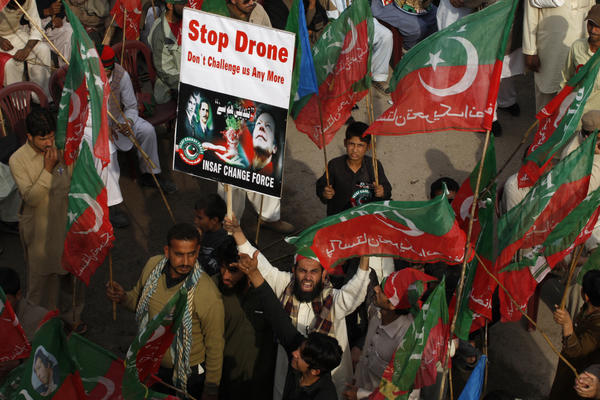Protesters in Peshawar hold up a poster and shout slogans during a demonstration Saturday against U.S. drone strikes in Pakistan.
