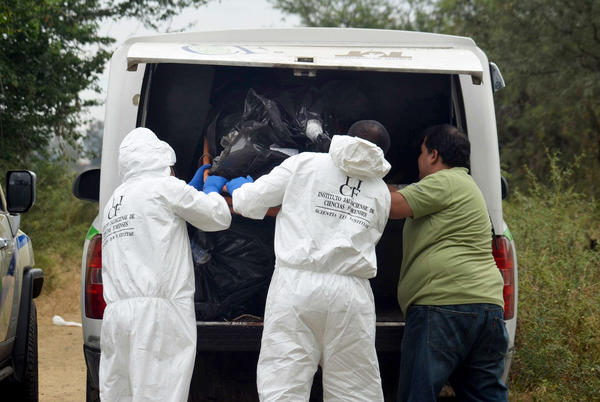 Forensic investigators put a body into a vehicle after recovering it from a mass grave in La Barca, Mexico.