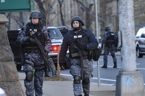 SWAT team members search the area around Calhoun College on Elm Street at Yale University in New Haven after an anonymous caller reported a gunman on campus Monday.