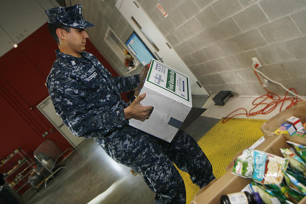 Sailors from the USS Abraham Lincoln are involved in many community activities while they are in port. They collected food and brought it to the Virginia Peninsula Foodbank. Here, MM1(SW/AW) Luis Rodriguez carries a box of donated food to a scale to be weighed.