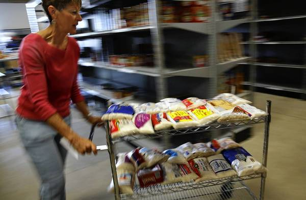 Food banks are seeking donations and volunteers. Above, volunteer Lani Orr pushes a cart of rice at the Families Forward warehouse-sized pantry in Irvine in May.