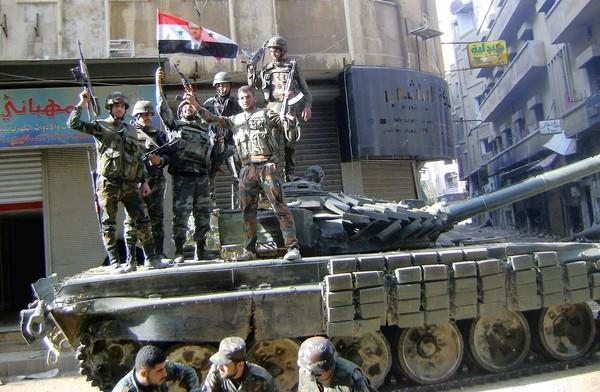 Government soldiers stand on a tank in Homs, a key battleground in the Syrian war. The United Nations announced that talks to end the war will begin Jan. 22 in Geneva.