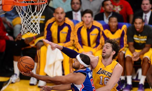 Clippers forward Jared Dudley, left, puts up a shot in front of Lakers forward Pau Gasol during each team's season opener in October. Dudley hasn't missed a game this season despite playing with tendinitis in his right knee.