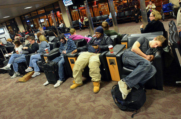 Travelers wait for a flight at Phoenix Sky Harbor Airport in Phoenix on Tuesday. As a winter storm moved toward the East Coast, the National Weather Service warned it would almost certainly upset holiday travel plans for those hoping to visit loved ones in the mid-Atlantic and Northeast.