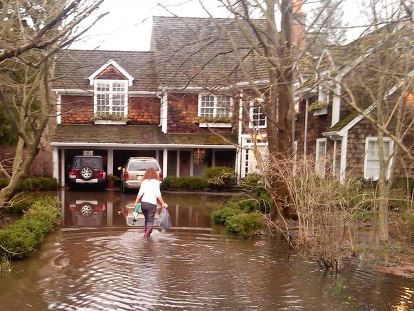 In Winnetka, residents will soon begin paying a stormwater utility fee devised to pay for a proposed $41 million stormwater management program. Here, Jan Bawden wades through flooding at her home on DeWindt Road in Winnetka after a storm this April.