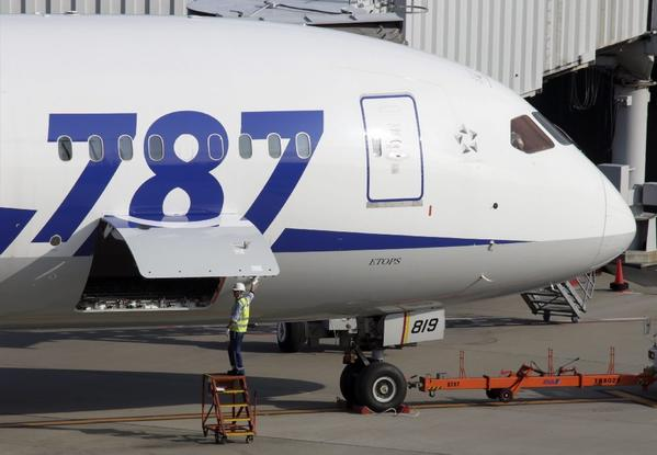 A member of ground staff of All Nippon Airways Co. closes a door near the battery room of a Boeing 787 Dreamliner before departure at Tokyo International Airport.