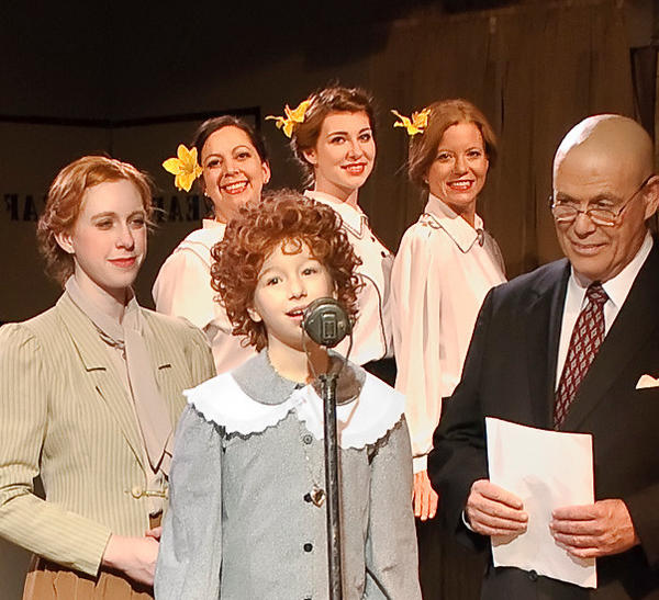 From left, Kaelynn Miller (Grace), Daphne EcKman (Annie) and Tim Sayles (Daddy Warbucks) make a radio plea in Annie, continuing through Dec. 8 at the Colonial Players in Annapolis. Behind are The Boylan Sisters, played by Lisa Rodvien, Natalie Nankervis and Tami Howie.