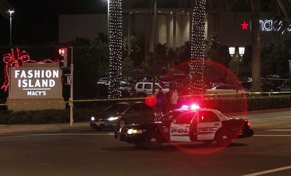 A police car blocks the entrance to Fashion Island following last year's shooting.