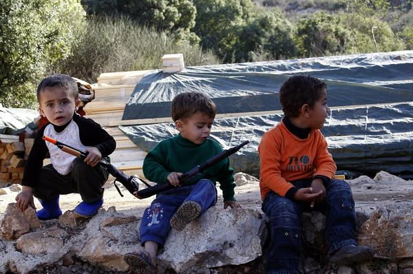 Syrian refugee children play with plastic weapons at a Syrian refugee camp in Ketermaya village, near Sidon, in southern Lebanon, on Tuesday. Peace prospects remain uncertain, despite a January date for peace talks in Geneva.