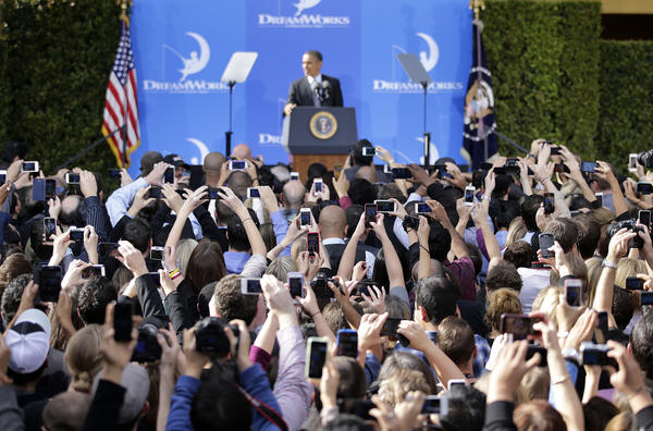 People take pictures of President Obama as he speaks at the DreamWorks Animation studio Tuesday in Glendale.