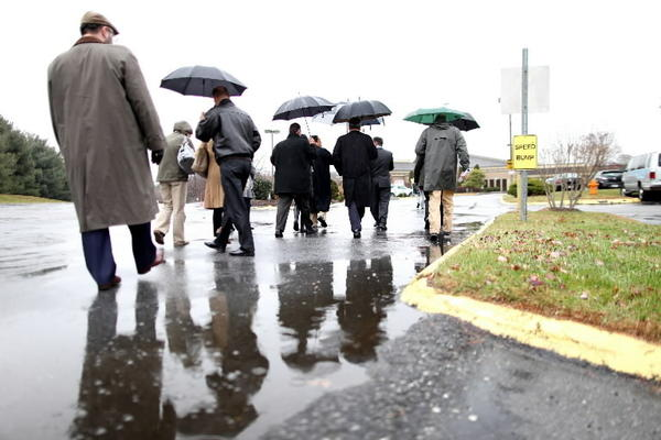 Officials walk across Bethel Korean Presbyterian Church parking lot after seeing where Howard County will pay to build swales and rain gardens to capture some rainfall runoff.