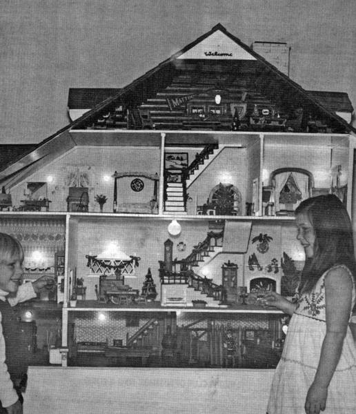 Siblings Lance and Heidi Adair admire the large doll house belonging to Mrs. Don Hicks of Cornishon Avenue, which would be displayed at the 1973 Descanso Gardens Christmas exhibit. The structure was built by a family friend in Minnesota in 1939 and presented to its owner when she was a child.