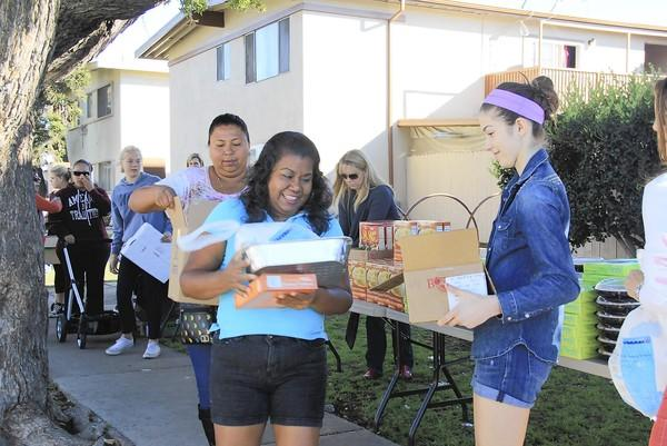 Volunteers from THINK Together and the National Charity League hand out Thanksgiving dinner supplies Sunday to residents in the Shalimar Drive area of Costa Mesa. The annual tradition was threatened this year but volunteers came together to make it happen.