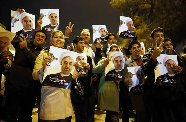 Supporters hold up photos of President Hassan Rouhani on Sunday evening as Iranian Foreign Minister Mohammad Javad Zarif arrived at Tehran's Mehrabad Airport after nuclear talks in Geneva.