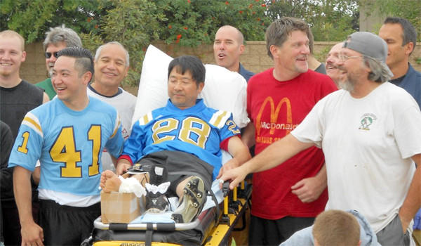 Ross Mishima on gurney, with teammates and the paramedics who tended to his broken ankle in last year's Mud Bowl.