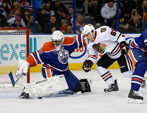 Oilers goaltender Ilya Bryzgalov makes a save against Andrew Shaw during the second period.