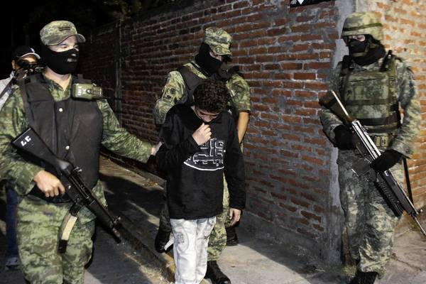 """Mexican soldiers escort Edgar Jimenez Lugo, known as """"El Ponchis,"""" in Cuernavaca, Mexico, at the time of his arrest in December 2010, when he was 14. Having served three years behind bars -- then the maximum for a minor in Morelos state -- Jimenez was released Tuesday and will soon be settling in the United States, where he was born."""