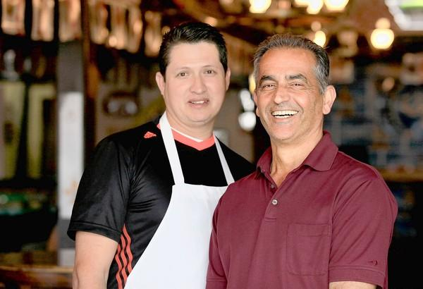 Owner Frank Tahvildari, right, and chef Abraham Ramos at Tumbleweeds Bar & Grill in Huntington Beach. Tahvildari will host his 18th annual free Thanksgiving meal on Thursday at Tumbleweeds Bar & Grill.