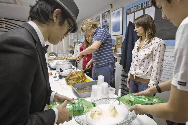 Crissy Werner, left, a speech pathologist, and Jennifer Gilleand, an aid, watch as Spencer Rabsten, 15, carves a turkey during a Thanksgiving meal for students in the Endeavor program at Marina High School on Friday. The program serves students with high functioning autism.