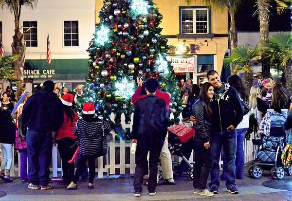 Residents gather around the Huntington Beach Christmas tree during a lighting ceremony in downtown on Sunday night.