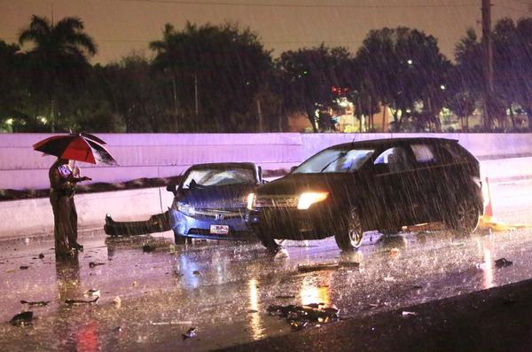 During a heavy rain storm, the Florida Highway Patrol investigates a multi-vehicle crash along I-595 near Davie Road that killed on man and sent two other people to the hospital early Wednesday, Nov. 27, 2013.