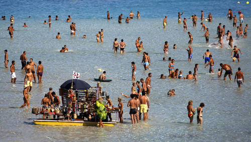 People sunbathe on the beach in the Italian town of Stintino, north west of Sardinia, August 9, 2010.