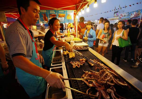 Seng Sivilay, left, and Spina Huang prepare food at their BBQ Squid stand in the Asia market in Richmond near Vancouver, British Columbia, Canada.