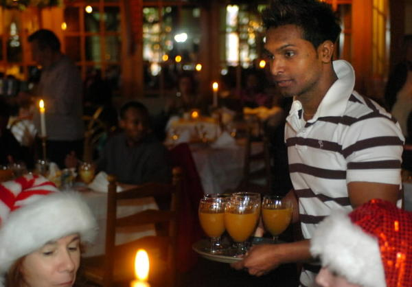 Raju Gomes, then age 21, serves apple cider during a 2005 Christmas Day dinner at Cavey's restaurant for residents of three homeless shelters. Gomes began the annual event as a high school senior.