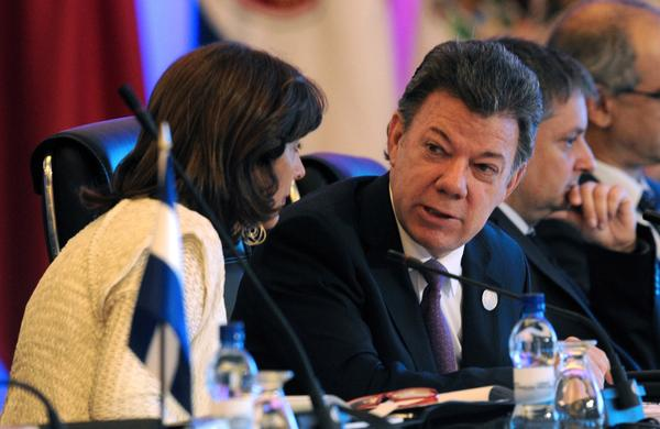 Colombian President Juan Manuel Santos speaks with Foreign Minister Maria Angela Holguin during the Ibero-American Summit in Panama City last month.