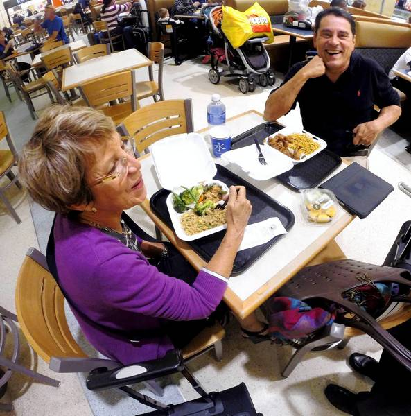 Travelers Jorge and Irma Suria, from San Juan, Puerto Rico, talk about healthy eating as diners snack at the food court at Orlando International Airport, Monday, Nov. 25, 2013.