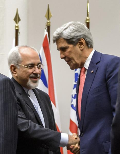 "Iranian Foreign Minister Mohammad Javad Zarif (2nd L) shakes hands with US Secretary of State John Kerry as they stand next to French Foreign Minister Laurent Fabius (R) after a statement early on November 24, 2013 in Geneva. World powers on November 24 agreed a landmark deal with Iran halting parts of its nuclear program in what US President Barack Obama called ""an important first step""."