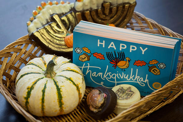 A wicker basket containing an assortment of chocolates decorated with both Hanukkah and Thanksgiving themes along with a stack of Thanksgivukkah greeting cards is displayed on a table at the Jewish Community Center in Tenafly, N.J.