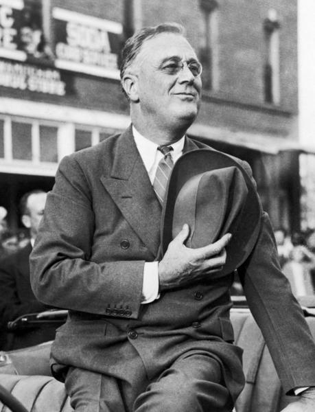 President Franklin D. Roosevelt salutes the flag during a parade, circa 1938.
