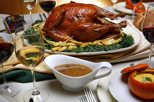 Salt-rubbed, roasted turkey with roasted parsnips, pan sauce, center and spiced pumpkin soup with maple syrup in roasted pumpkins, are part of the Thanksgiving dinner table.